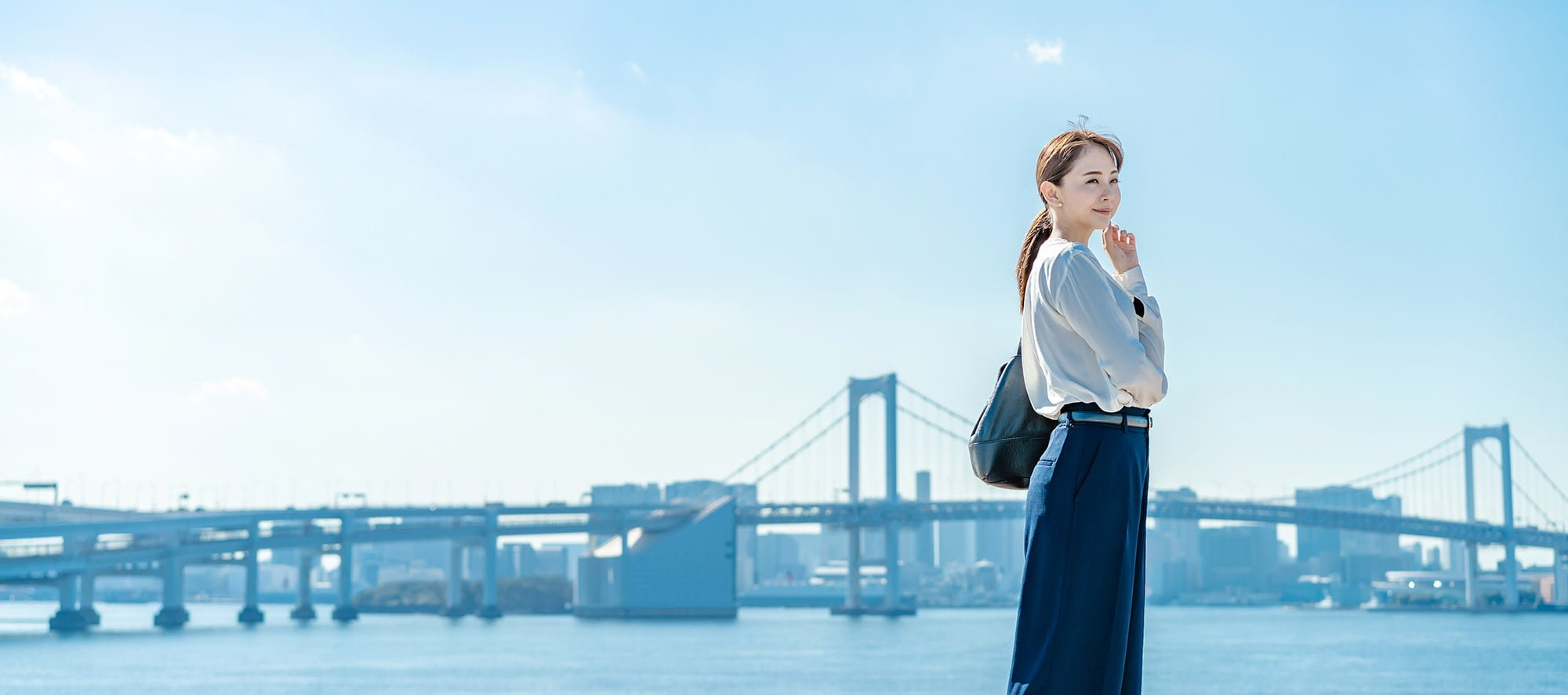 a girl with blue sky and bridge in backgrournd