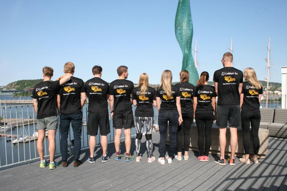 backs of ten runners wearing blach t-shirts with paperseed foundation logos