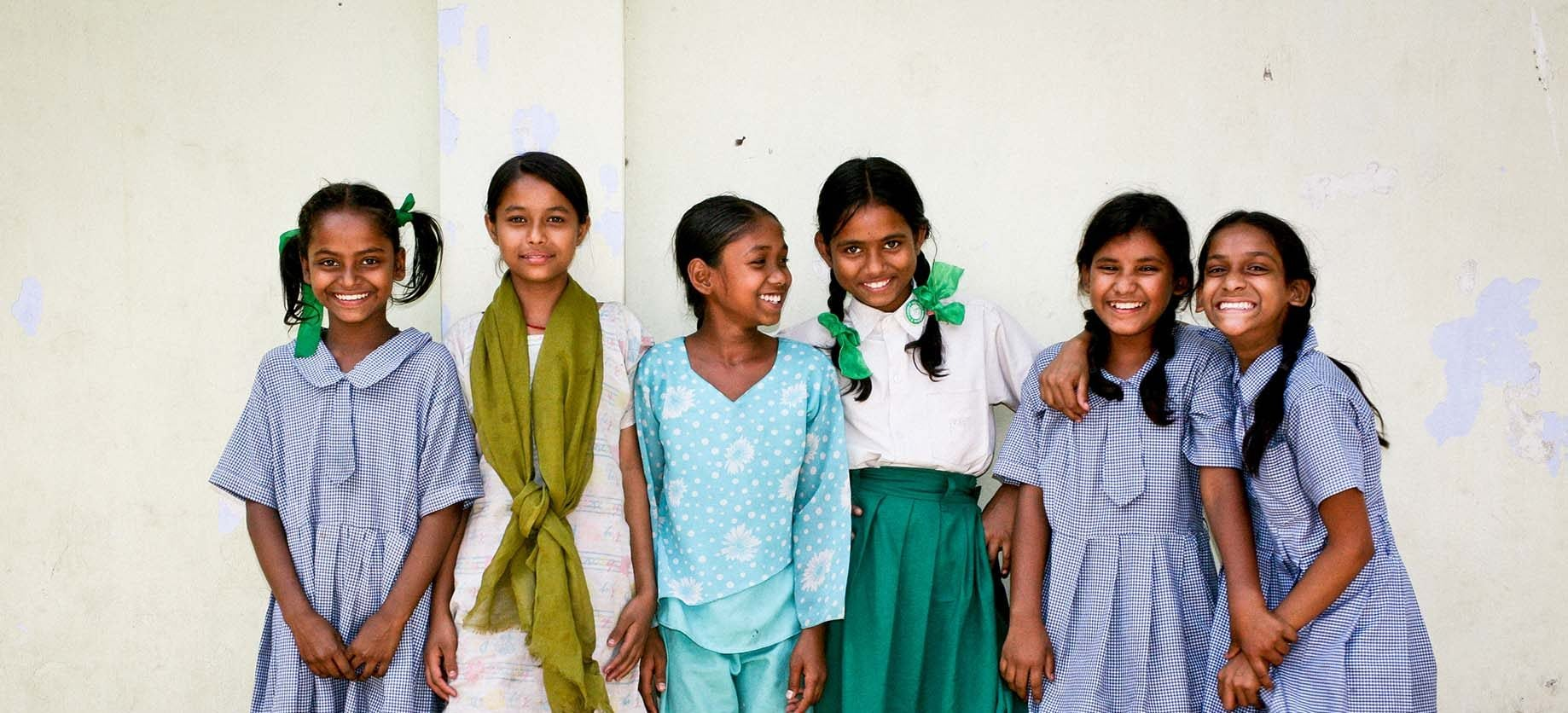 young girls in colorful clothes smiling into the camera