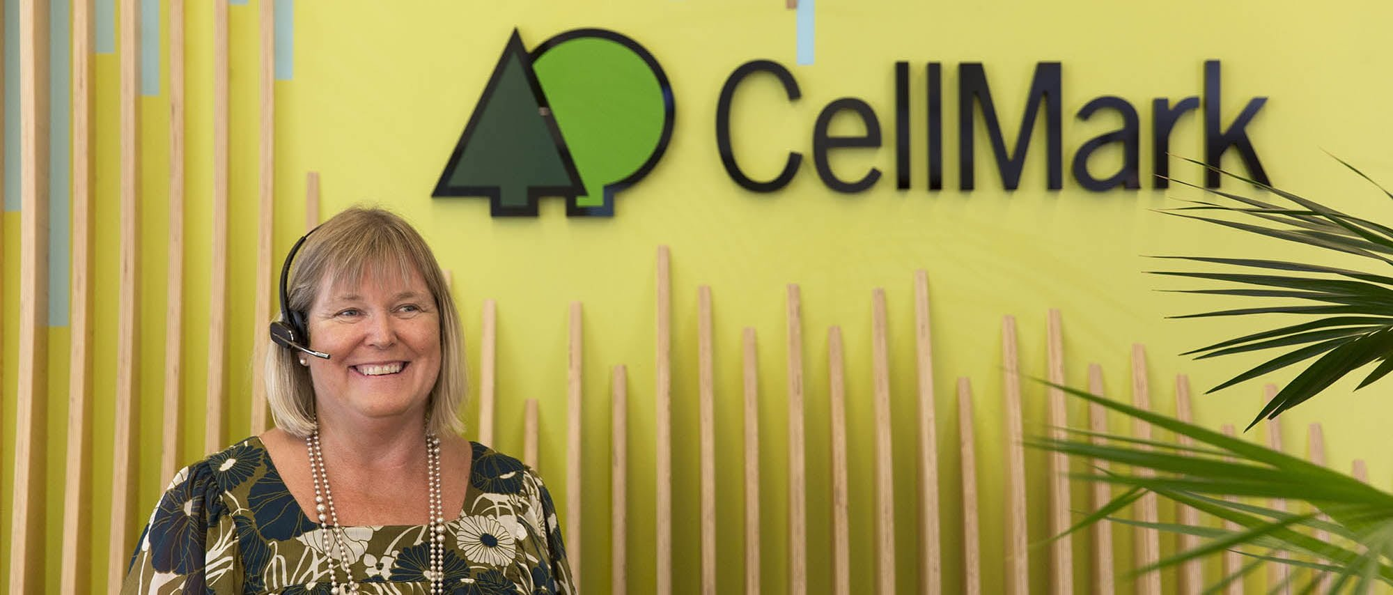 smiling receptionist woman in front of cellmark logo wall